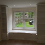 A window seat with cupboards and shelves